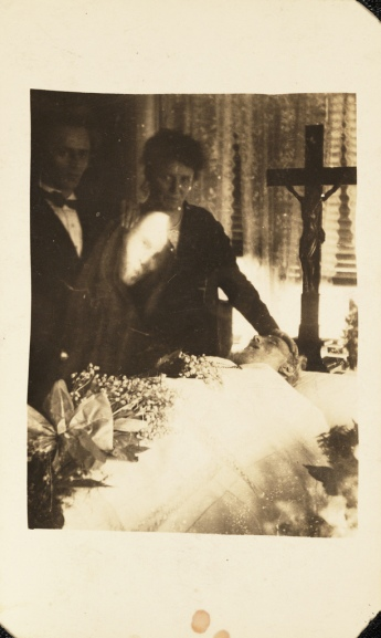 Vintage mourning scene with ghostly face, 1920