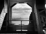 A man peers across the Hudson River into Manhattan from his perch on the George Washington Bridge on December 22, 1936