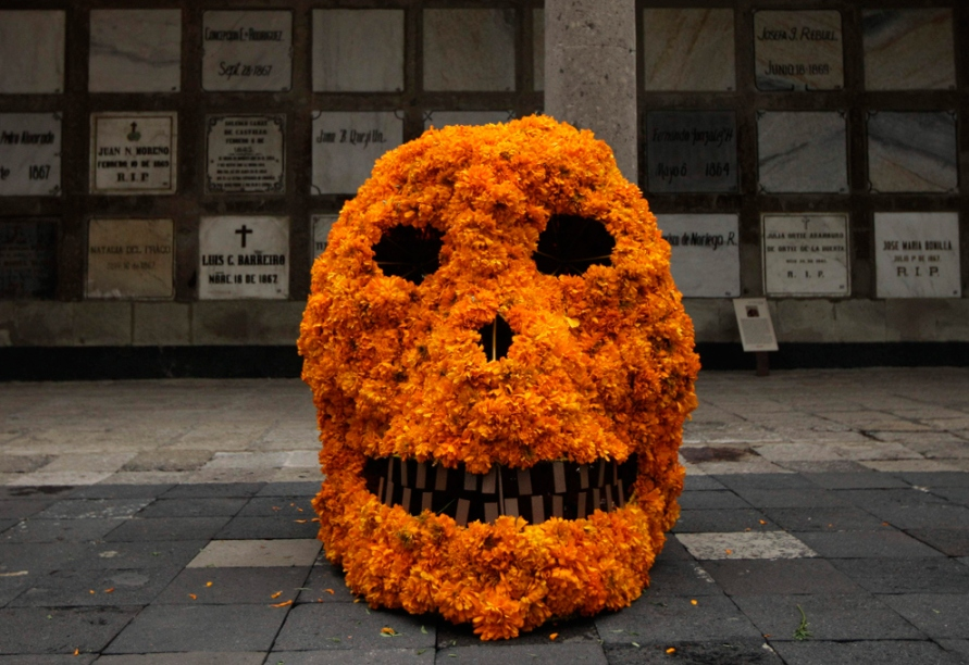 A skull covered in marigolds rests in front of a wall of graves, Mexico City, Oct. 27 2009 Halloween Day of the Dead Dia de los Muertos